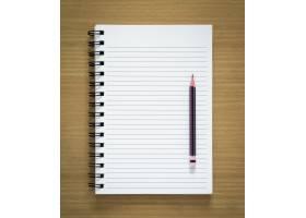 木质背景上的空白螺旋记事本和铅笔_1164004