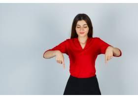 穿着红色上衣和裙子的年轻女士指着下面看_11620882