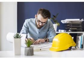 有魅力的男性工程师在工作场所绘制蓝图_2601884