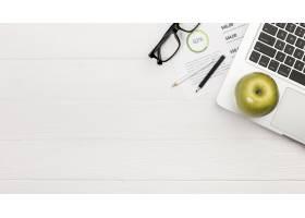 笔记本电脑上的绿苹果桌上放着彩色铅笔和_4767660