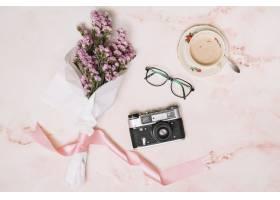 桌子上有带相机和咖啡的花束_3764590