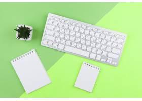 绿色背景上的顶视文具排列带空记事本_5410516