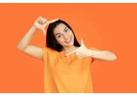 橙色工作室背景下的高加索年轻女子肖像_13455981
