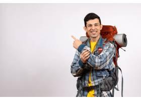 正面愉快的年轻旅行者背着背包指着后面_13461483