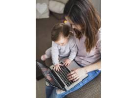 母亲使用笔记本电脑与孩子坐在一起的俯瞰_2602014