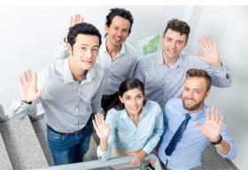 微笑的商务团队在办公室楼梯上挥手_1305416