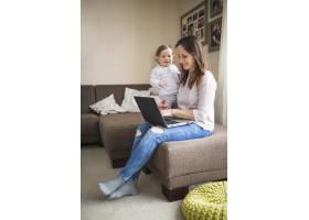 微笑的女人和她的女儿在笔记本电脑上工作_2593115