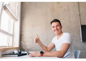 年轻英俊的微笑着的男人穿着休闲装坐在桌子_9699671