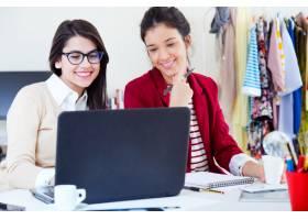 在笔记本电脑上工作的年轻女商人_1093476