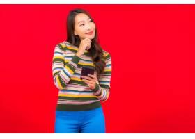 在红墙上用智能手机为美丽的亚洲年轻女子画_12045252