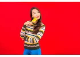 在红色隔离墙上画有信用卡的美丽亚洲年轻女_12045259