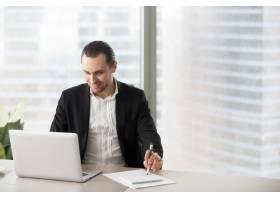 开心的微笑着的商人在办公室看着笔记本电脑_4013275