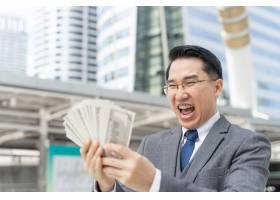 开心脸亚洲商人手持美元钞票在商业区富城_11872311