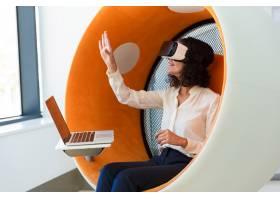 开朗的女商人手持笔记本电脑观看虚拟演示_5889833