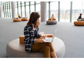 坐在机场休息室时使用笔记本电脑的快乐女人_13258854