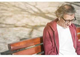 坐在板凳上的戴着无线耳机面带微笑的老人_3442411
