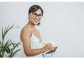 微笑的女商人摆姿势在日记上写字_1203944
