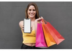 微笑的女孩拿着购物袋拿着手机_5498442