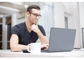 微笑的年轻帅哥在笔记本电脑上工作_1305577