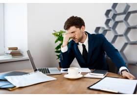 心烦意乱的年轻商人坐在工作场所办公室背_7855195