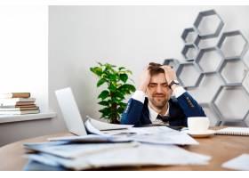 心烦意乱的年轻商人坐在工作场所办公室背_7855282