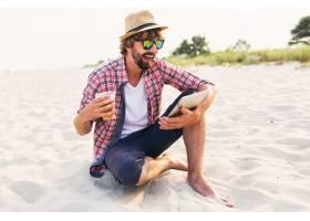 快乐时髦的男人在海滩上用平板电脑喝啤酒_9686758