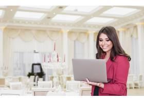 快乐活动经理在宴会厅使用笔记本电脑_4191548