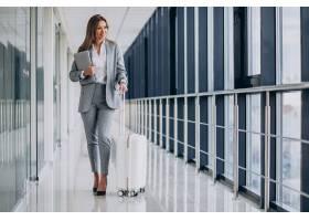 女商人在机场提着旅行行李手持笔记本电脑_7200208