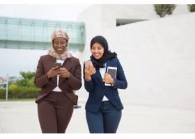 快乐的办公室女性朋友在外面用智能手机聊天_5890403