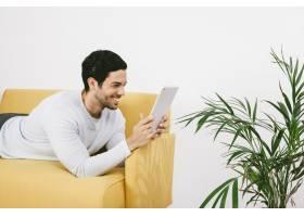 快乐的年轻人躺在沙发上看着平板电脑_1203469