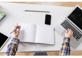 女性在笔记本上写字的手和笔记本电脑的触摸_4233560