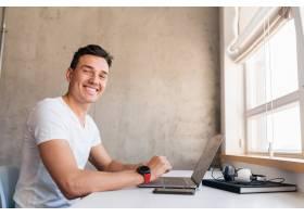 快乐的年轻英俊微笑的男人穿着休闲装坐在桌_9699669