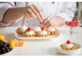 女性糖果师手在奶油馅饼上的特写_1281913