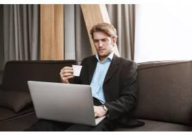 优雅的没有刮胡子的男人喝着咖啡看着笔记_9029225