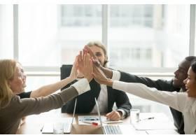兴奋快乐的多种族商业团队在办公室会议上击_3939799