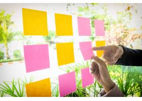 办公室内一名女子在玻璃墙上贴胶条的手的特_1202389