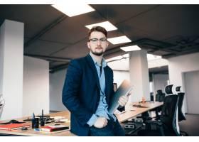 办公室里一位戴着眼镜的帅哥正站在工作场_9960960