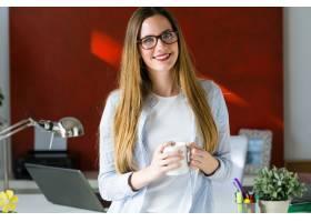 一位年轻漂亮的女士在办公室里喝咖啡_1151982