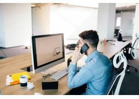 一位年轻的黑发男子正在办公室的台式电脑前_9960980