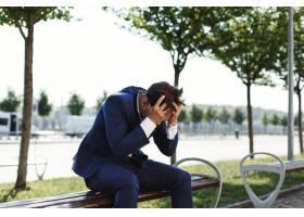 一位悲伤的商人坐在街外的银行上_2612712