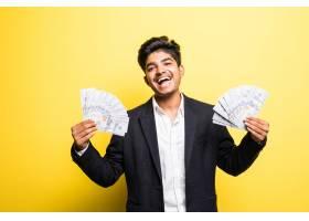一位成功的印度企业家手里拿着美元钞票_9076723