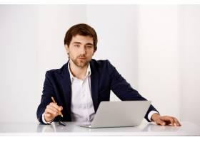 一位成功的商人坐在办公室里拿着笔记本电_9226870