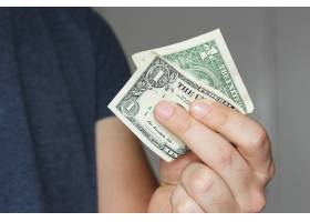 一个人手上拿着一张美元钞票的特写镜头_10292316