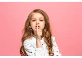一个年轻的少女在隔绝在时髦的粉色工作室墙_13056263