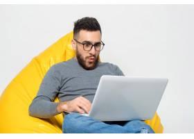 一个男人坐在黄色的折叠椅上大吃一惊_7608104