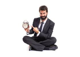 一位商人在白色背景上拿着一只钟_1200227