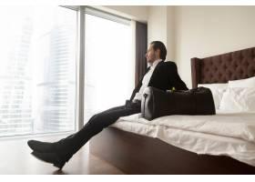 一位轻松的商人坐在床上旁边是行李袋_4013386