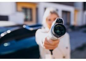 一名女子在家中为电动车充电并拿着充电器_6190044