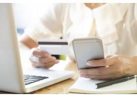 一名女子在笔记本电脑上拿着手机和信用卡进_1236539
