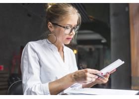 一名年轻女子在餐厅处理文件_2804440